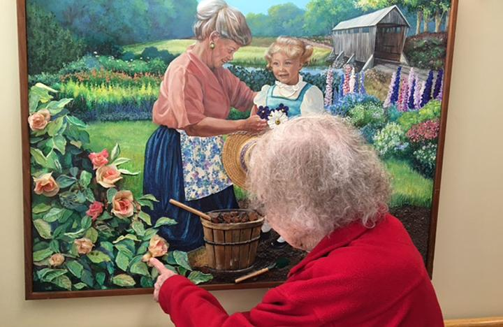 A Memory Care resident enjoys looking at a painting in the Care Center