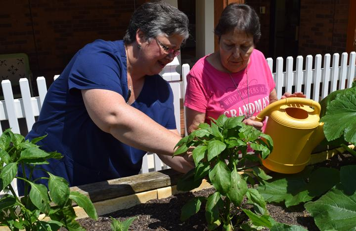 A Caretaker and Memory Care resident tend to the garden