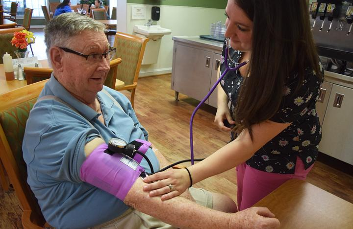 An Assisted Living resident gets his blood pressure checked