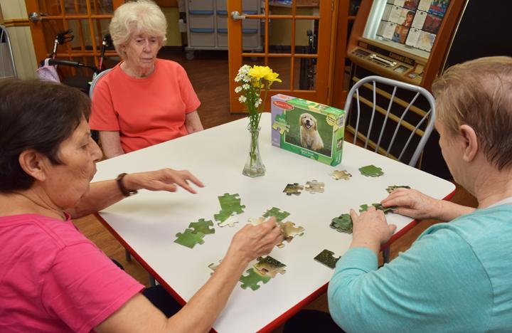 Memory Care residents enjoy a puzzle