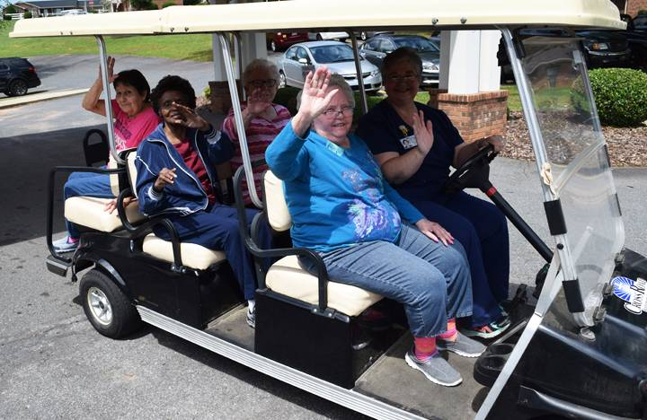 Memory Care residents enjoy a ride on a golf cart