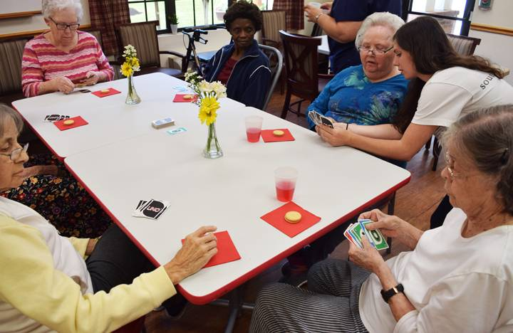 Memory Care residents enjoy a round of UNO