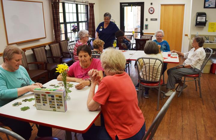 Memory Care residents gather in the activity room for some social time